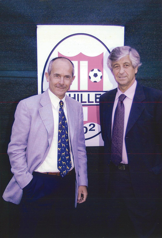 Foto ricordo del presidente dell'Achillea Paolo Luzi e Gianni Rivera davanti allo stemma di Achillea 2002